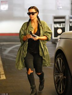 Chic Kim: Kim also wore torn jeans and lace-up high tops giving her an edgy urban look. The Keeping Up With The Kardashians star wore a green army zip-up parka over her jeans and T-shirt combo