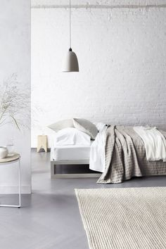 White wash brick wall, rug, grey floors and neutral bed linen with feature concrete pendant light. Love.