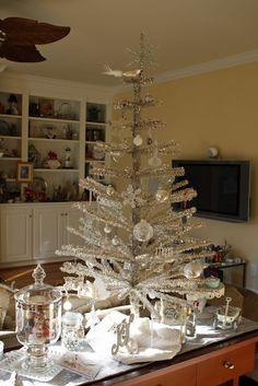Put a little tree on a table to make bigger statement.   33 Exciting Silver And White Christmas Tree Decorations | DigsDigs