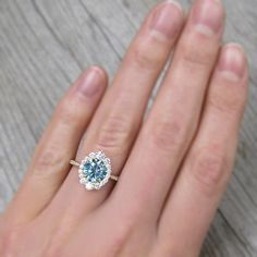 A vintage-inspired halo ring design featuring a aqua-teal Iconic Moissanite, with a lab-grown diamond or Canadian mined diamond halo. This shade of blue colored moissanite is a more durable, sparkly, and brilliant alternative the aquamarine gemstone. Perfect Engagement Ring, Engagement Rings, Aqua Wedding, Marital Status, Moissanite Diamonds, Aquamarine Gemstone, Emerson, Halo Diamond, Coffin
