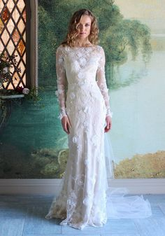This Romantique by Claire Pettibone Prarie Rose gown features re-embroidered lace scattered with hand beaded organza flowers and delicate pearls. This design features an elegant bateau illusion nec...