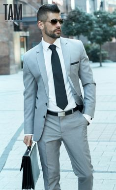 Grey suit mens fashion. Paired with a crisp white shirt, dark green tie, briefcase and sunglasses for the ultimate light business fashion look.