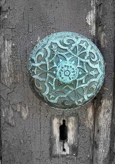 Uma porta marcada pelo tempo, com maçaneta.