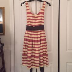 Anthropologie Pink and Cream Striped Dress This is a pink and cream CoreyLynnCalter dress purchased at Anthropologie. It is fitted at the top and flares out with pleats from the waist. Has an attached navy blue belt. Dress zips up the back and is lined. It is about 17in across the pit, 15in across the waist and 35.5in long. Anthropologie Dresses