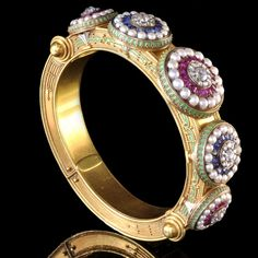 """Rare and impressive bangle by Giuliano, circa 1880. Diamonds, rubies, sapphires and seed pearls, all set in yellow gold with gold wire and enamel detailing."""