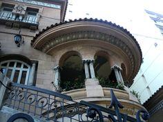 """O vestíbulo é o grande espaço de distribuição entre os pavimentos. Possui uma escada em forma de """"U"""", de madeira; o arranque é um pitoresco ornato de estuque com formas sinuosas e rosto de mulhe"""