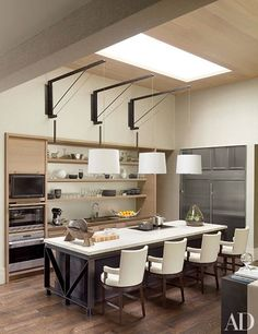 At a Tennessee home, which was renovated by the architecture firm DA|AD and decorated by McAlpine Booth & Ferrier Interiors, shelving is suspended above the kitchen sink.