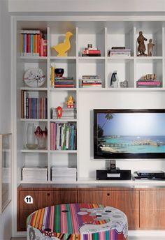 11. Encaixadas sob a estante da TV, gavetas de nogueira ocultam CDs, DVDs e até louças. Esta parte do móvel foi projetada com dimensões de banco (30 cm de profundidade x 50 cm de altura) e funciona como assento nas festas. Futon Company e a Tsuruya. As duas lojas têm bastante variedade
