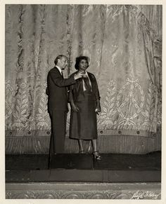 "View of contralto Marian Anderson standing onstage with Metropolitan Opera general manager Rudolf Bing. Printed on front: ""Sedge LeBlang."" Stamped on back: ""Sedge LeBlang, photographer for the Metropolitan Opera, 147 West 39th St., N.Y. 18, N.Y. PE. 6-8640."" Handwritten on back: ""Rudolf Bing, Metropolitan general manager, with Marian Anderson after signing of Met contract, Oct. 7, 1954."" Marian Anderson, Leaving A Legacy, A Hundred Years, Metropolitan Opera, My Lord, Conductors, African, Singer, Printed"