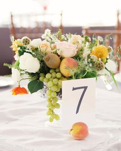 Since the color palette of the wedding was inspired by the bride's love of summer peaches, the fruit itself was incorporated in each table's centerpiece. They took centerstage holding table numbers, and were subtly mixed in the floral centerpieces, along with other fruit like kiwis and green grapes.