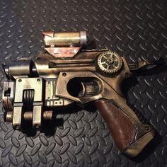 Steampunk Cosplay Nerf Gun mousse Blaster Ray pistolet, jeu de tir à la main peint Prop, or avec cuir enroulé adhérence et à la main en métal portée  Détails :  Ce laser ciblant Nerf gun (lorsque lon tire sur cible montre rouge détente dans la région de votre pointage) elle est peinte pour ressembler steampunk / diesel style punk avec de l'or peint détaillant, engrenages sur les deux côtés en cuivre et poignée en cuir. Également équipé d'un tout métal cuivre et laiton.  Grande addition à...
