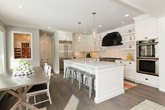 Warm white kitchen.  Marble countertops.  Open shelving.  Grey washed wood floors.  Minus hood.