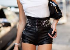 white t-shirt. black leather shorts with studs. black clutch.