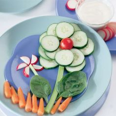 Flower vegetable design with baby carrots, celery, baby spinach, radish, cucumber, and a cherry tomato