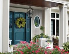 Porch ceiling stained the same color as the front door?  Love the dark wood look here.
