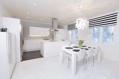keittiö,valkoinen,moderni,liesituuletin,verhot,ruokapöytä,design,ruokailuryhmä,valaisin,valoisa,avara,minimalistinen