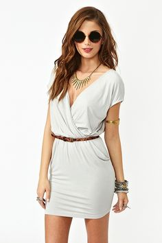 Easy breezy silver wrap dress featuring a plunging wrap top and cutout back. Hip pockets, stretch panel at waist. Unlined. Perfect paired with a wide brim hat and platform boots!