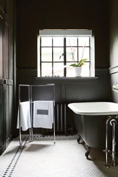A dark retreat that reads as sophisticated, not gloomy.    Matte black paint on panelled walls, paired with a black clawfoot tub, is an unexpectedly elegant and refreshing change from predictable, white marble bathrooms. French door-style windows add even more high-end appeal.