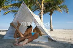 Stock Photo : Two young women lying in tent on beach, rear view