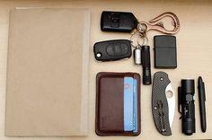 SaddleBack Leather ID Wallet••Spyderco Sage 1••Matte Black Zippo Lighter••Olight M10 Maverick••Fisher Space Pen Bullet••iPhone 4••Book••Corter Leather Bottle Hook••SS Split Pea Lighter••Fenix E05
