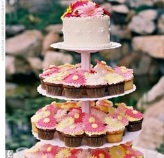 """The cake was one of the couples' favorite parts of the wedding -- they chose a multi-tiered confection made of vanilla and chocolate cupcakes, adorned with frosted gerbera daisies on top. """"There were enough cupcakes for people to snack on at the wedding,""""..."""