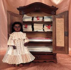 """Theriault's Antique Doll Auctions - French Doll's Wooden Armoire with Linens and Original Inventory 23"""" (58 cm.) - Fine walnut wood armoire with paneled double doors,arched crest with ogee carving,lower drawer,fine silver lock and key,opens to reveal four well-stocked linen shelves,and a list of """"composition de trousseau"""" on the inside door,listing various house linens and accessories. French,circa 1890. The fitted armoire was a popular offering in holiday Etrennes catalogs of the era in…"""