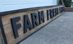 Sign made from salvaged boards. Letters are cut out with a jig saw and painted with flat black paint.