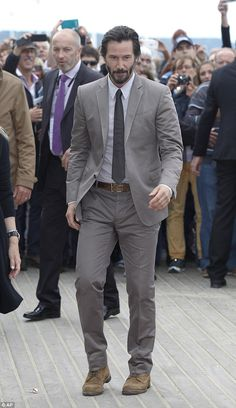 Casual touch: The 51-year-old teamed his sharp grey suit with a pair of rugged suede shoes...