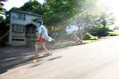 Longboarder skating on an urban road with lens flare while being filmed by another man. Slight motion blur from panning technique to capture movement
