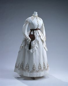 1867-1868 -England, White cotton piqué set of bodice, skirt and overskirt; code embroidery of ocher brown cotton threads; metal buttons at front; brown silk taffeta chatelaine.  Kyoto Costume Institute