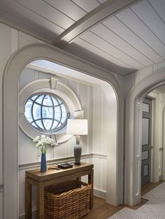 Gorgeous upstairs hall in a beachfront house in Quogue, NY by Robert A.M. Stern Architects with interiors by Steven Gambrel. The fact that that oval window is operable is everything.