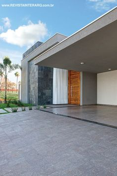 Detalhe da fachada com textura mais escura acompanhando o revestimento de pedras Antiqua Negra e o piso em porcelanato rústico