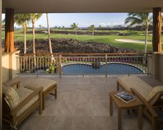 While you do live right next to a golf course, not many people would complain about that view. Remodeled patio located on the 2nd floor balcony features chaise lounge chairs, brown tile floor and a metal and wood guard rail. Would you like this patio?
