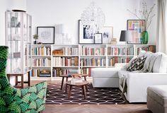 La habitación durante el día. Sofá, sillón, librerías, alfombra, mesas de centro…