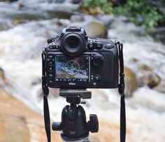 A DSLR camera in front of a whitewater river.