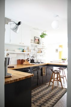 Dark cabinets, butcher block top and white upper cabinets