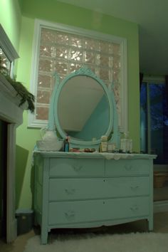 Bedroom with soft green walls and a painted vintage dresser painted in Aqua blue from designer www.janehalldesign.com