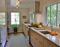 Our small galley kitchen is not just for show.  Floor to ceiling cabinets store everything from dishes and pantry items to the microwave. With two sinks, one main and a second as a produce - wet bar off the dining room, the kitchen functions much larger than its small 150 square feet.