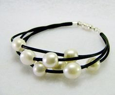"""Pearl bracelet had 4 strands of brown or black leather with 8 cultured pearls~ 2 on each strand ~ and has a silver magnetic clasp. Just message me if you want brown or black leather. Fits 6 1/2"""" - 8"""" wrist."""