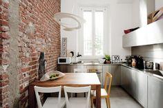 small apartment - loft - white - gray - concrete floor - resin floor - steel kitchen - professional kitchen - artemide - livia chair - gio ponti - bricks wall