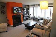 the bright orange accent wall works great with the black fireplace.