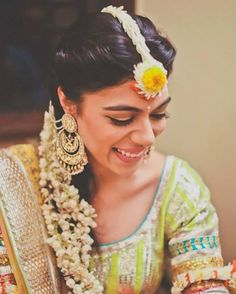 Floral jewellery goals. Bride Malvika Singh looks lovey in an adorable floral maangtikka and mogra twisted around her braid for her mehendi ceremony.