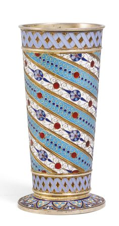 A Russian silver-gilt and cloisonné enamel beaker, Antip Kuzmichev, Moscow, 1895, the flared body wrapped with alternating turquoise and white ground bands of foliage, translucent red pellets and cloison scrolls, the rim and base borders with interlacing blue straps, the underside of the base engraved with initials BNC.