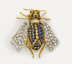 A sapphire, emerald and diamond bee brooch with hinged wings and emerald eyes; estimated total sapphire weight: 2.25 carats; estimated total diamond weight: 0.95 carat; mounted in eighteen karat bicolor gold; length: 1 9/16in.