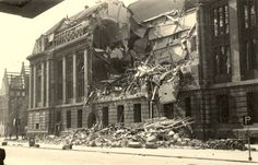 Het gebombardeerde postkantoor te Rotterdam. Bommen die op de Meent vielen beschadigden het postkantoor ook. Op de onderste ramen aan de linkerkant van de gevel zitten nog de metalen platen die ter bescherming konden worden aangebracht. Tegen zoveel geweld als de bommen die op de 14e mei vielen, waren evident ook de metalen platen onvoldoende. Links om de hoek is de Coolsingel.