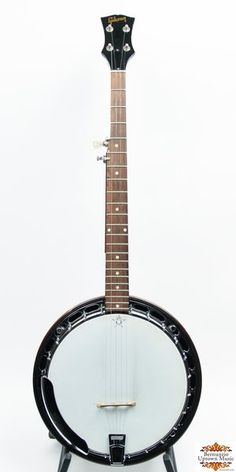 This is a stock RB-100 with the thinner, black rim with gold label and single piece flange. The banjo was fitted long ago with an old, no hole flat top tone ring and newer tuners. This is a fine player with a great sound.