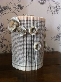Shabby Chic recycled book table centerpiece - maybe a fluff of baby's breath or one hydrangea bloom coming out of the top...
