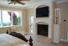 """Master bedroom with gas fire place,  all marble hearth, custom wood mantel topped by built in 42"""" plasma TV..."""