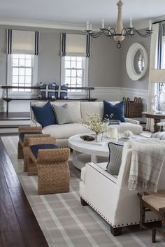 Crisp white sofas, navy blue accesories and natural ottomans VT Interiors - Library of Inspirational Images