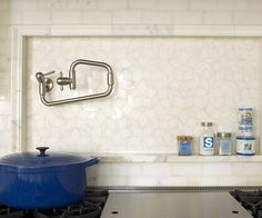 This range backsplash demonstrates how to add style and texture without using a dramatic color. Marble subway tiles adorn the wall behind the range. Mitered tiles made of the same marble create a frame around the behind-the-range niche, which is outfitted with shimmering marble tiles in various shapes and sizes./